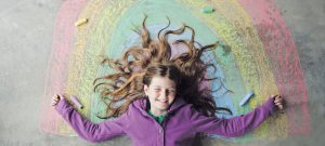 Communicating to planet conscious families: photo of young girl lying on the floor surrounded by a chalk rainbow